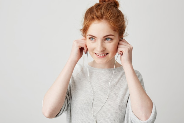 Portrait of young cheerful redhead girl smiling putting on headphones .
