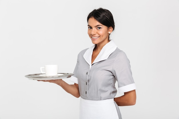 Portrait of young cheerful woman in gray uniform holding metal tray with cup of coffee