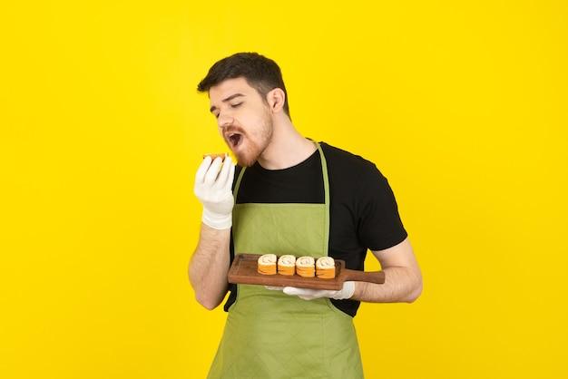 Ritratto di giovane chef che cerca di mordere il rotolo di torta su un giallo.