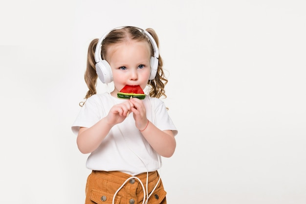 Portrait of young child girl in headset eat candy