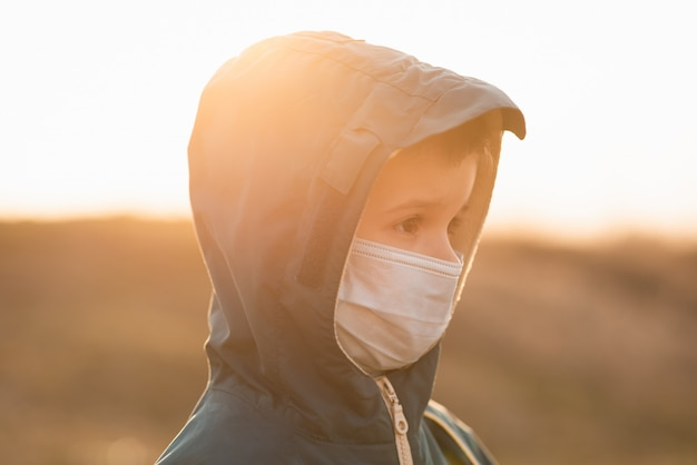 Portrait of a young child in a medical mask on the street during the coronavirus and covid pandemic - 19
