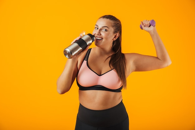 Portrait of young chubby woman in sportive bra drinking water from thermos while lifting dumbbell, isolated over yellow background
