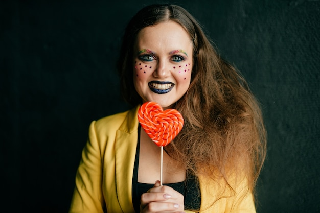 Portrait of young clown girl posing with sweet