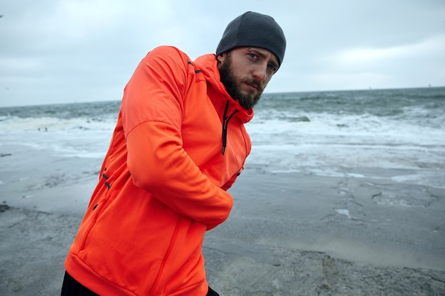 Portrait of young concentrated brunette bearded sportsman dressed in athletic clothes doing stretching exercises while standing over seaside on grey early morning