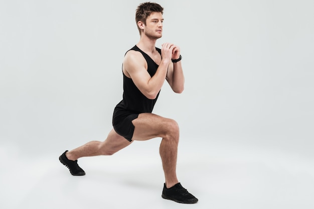 Portrait of a young concentrated man doing squats exercise