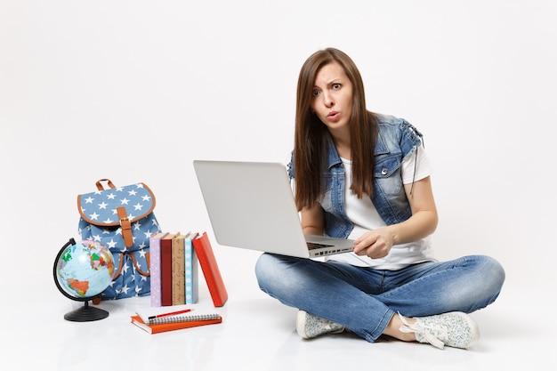 Ritratto di giovane studentessa casual preoccupata che tiene in mano un computer portatile seduto vicino al globo, zaino, libri scolastici isolati