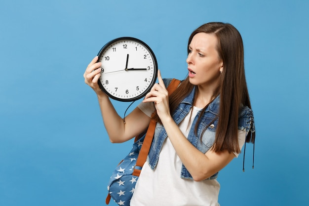 Portrait of young concerned dissatisfied woman student with backpack hold look on alarm clock isolated on blue background. time is running out. education in high school. copy space for advertisement.