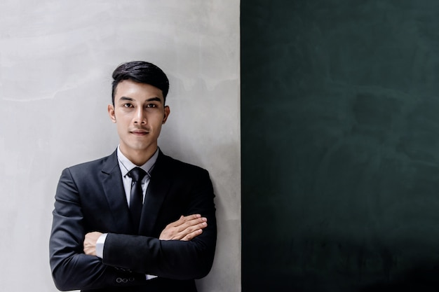 Portrait of young confident businessman in black formal suit.