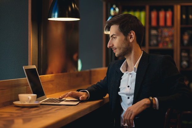 Portrait young confident businessman looking to laptop screen