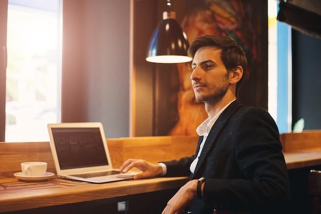 Portrait young confident businessman sitting near window