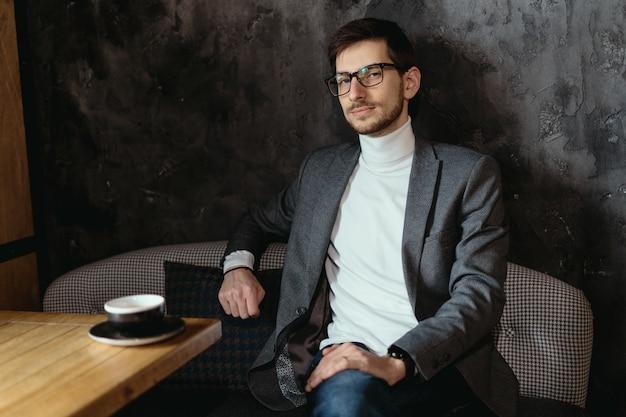眼鏡をかけている肖像画の若い、自信を持っているビジネスマン