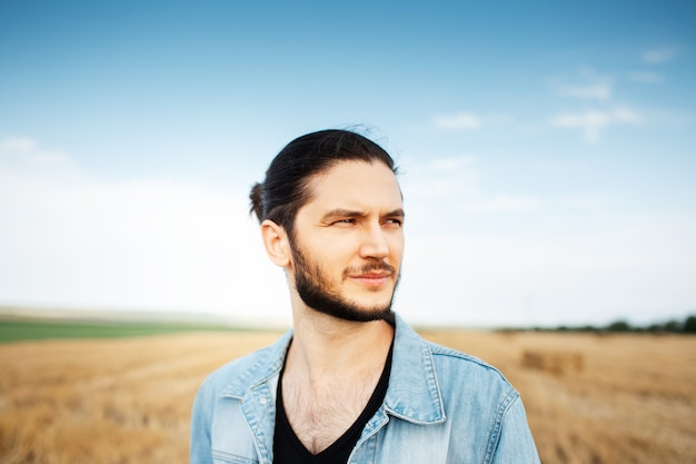 Portrait of young confident guy on background of blurred sky and hay field.