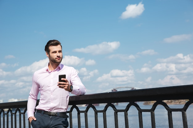 Portrait of young confident man using smartphone near river