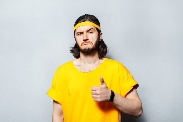 Portrait of young confident man in yellow shirt showing thumb up.