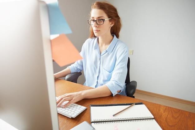 Ritratto di giovane imprenditore donna fiduciosa digitando sul computer portatile