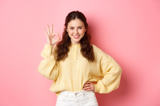 Portrait of young confident woman smiling pleased, say yes while showing okay sign, give approval, praise excellent choice, standing against pink wall.