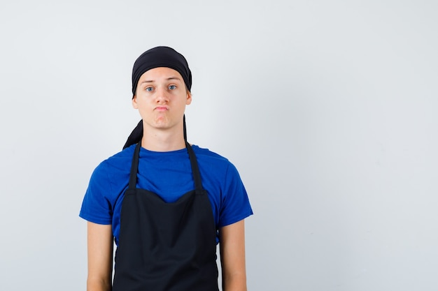 Ritratto di giovane cuoco in posa mentre si trova in maglietta, grembiule e guarda una vista frontale esitante
