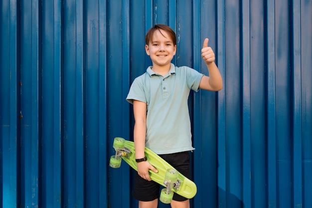 ペニーボードを手にポーズをとって青いポロの少年クールな笑顔の少年
