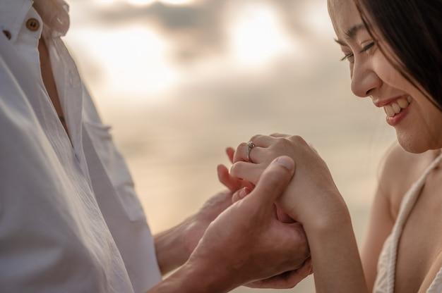 肖像画の若いカップルがsunsetsummerのビーチでガールフレンドと結婚する恋に