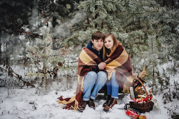 Portrait of young couple in blanket at the picnic on the valentines day in a snowy park. man hug girl in forest. concept mulled wine, hot tea, coffee. christmas holiday, celebration. happy new year.