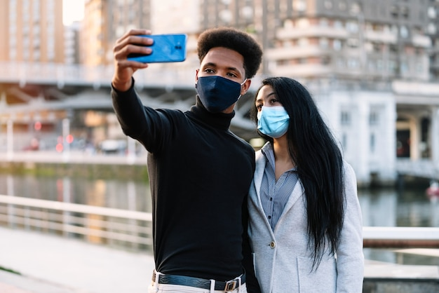 Portrait of a young couple boy style afro on the street taking a mobile phone selfie because they are visiting bilbao with a face mask due to the coronavirus pandemic