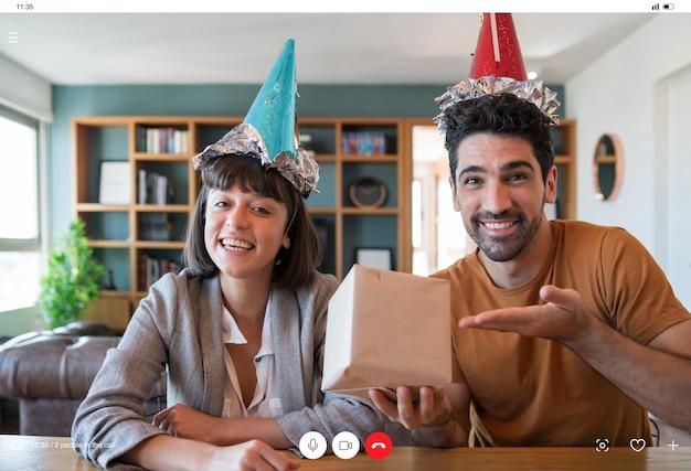 Ritratto di giovane coppia che festeggia il compleanno in una videochiamata con confezione regalo da casa Foto Gratuite