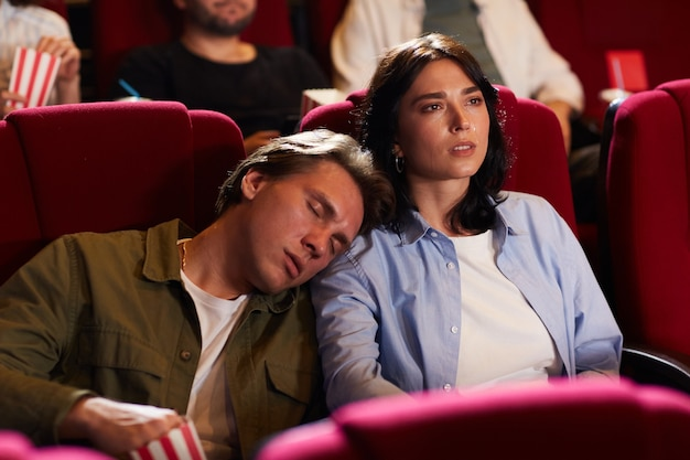 Portrait of young couple in cinema, focus on woman watching movie with bored boyfriend sleeping on her shoulder, copy space
