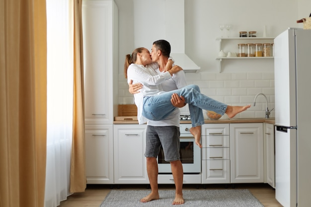 Portrait of young couple in a cosy kitchen, guy and the girl kiss and hug, man holds a woman in his arms, spending time together, honey moon, romantic feelings.