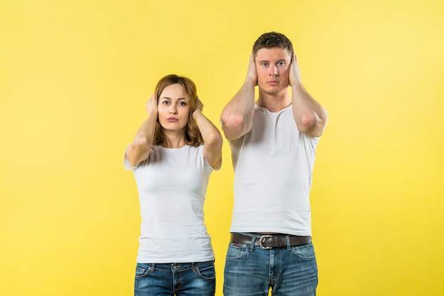 Portrait of young couple covering their ears against yellow background