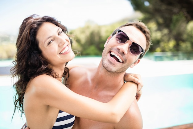 Portrait of young couple cuddling each other near pool at sunny day
