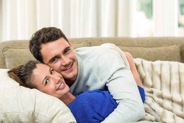 Portrait of young couple cuddling on sofa in living room