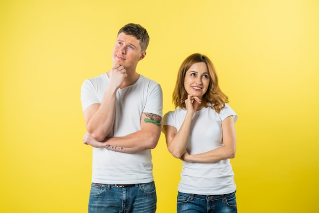 Portrait of a young couple daydreaming against yellow background