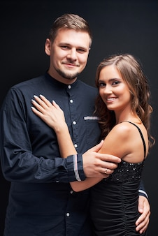 Portrait of young couple in elegant evening clothes isolated on black