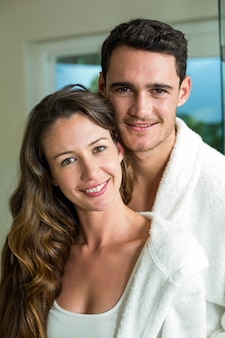 Portrait of young couple embracing at home