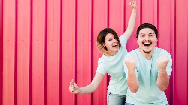 Portrait of young couple enjoying with joy against red corrugated backdrop