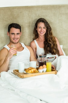 Portrait of young couple having breakfast on bed in bedroom