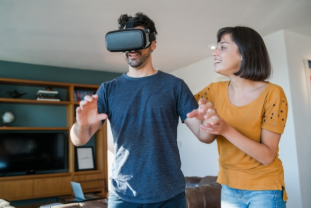 Portrait of young couple having fun together and playing video games with vr glasses while staying at home. new normal lifestyle concept.
