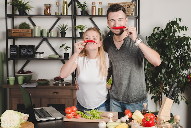 Portrait of young couple holding red chili over nose in the kitchen