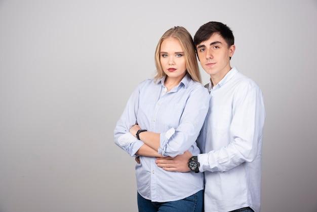 Ritratto di giovane coppia che guarda contro il muro grigio.