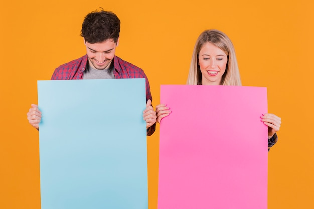 Portrait of a young couple looking at blue and pink placard against an orange backdrop