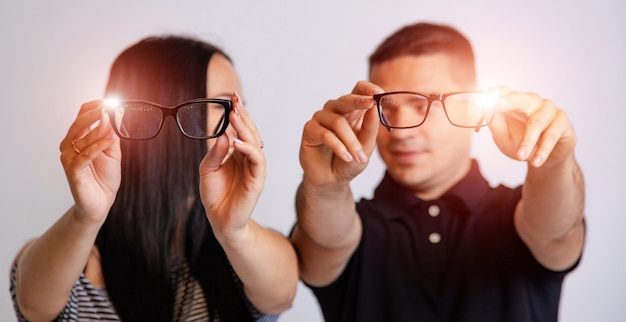 Portrait of a young couple looking through glasses isolated on white. presenting spectacles