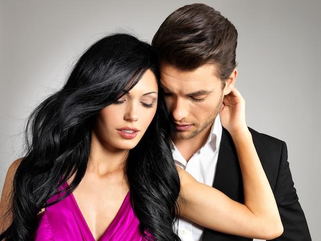 Ritratto di giovane coppia innamorata in posa in studio vestito con abiti classici