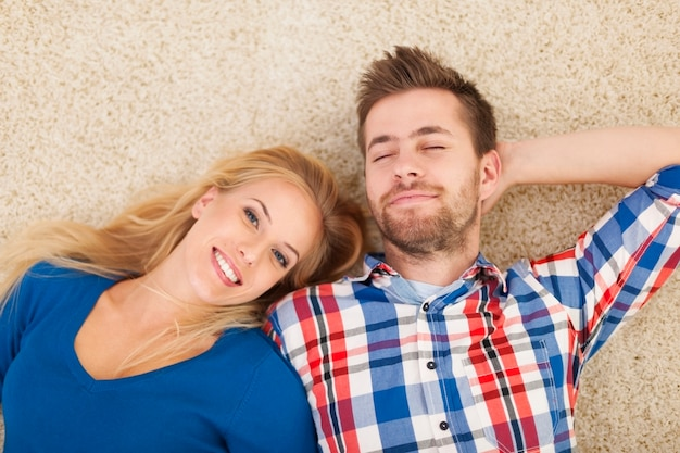 Portrait of young couple lying down on carpet