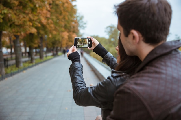Portrait of a young couple making photo on smartphone of autumn park