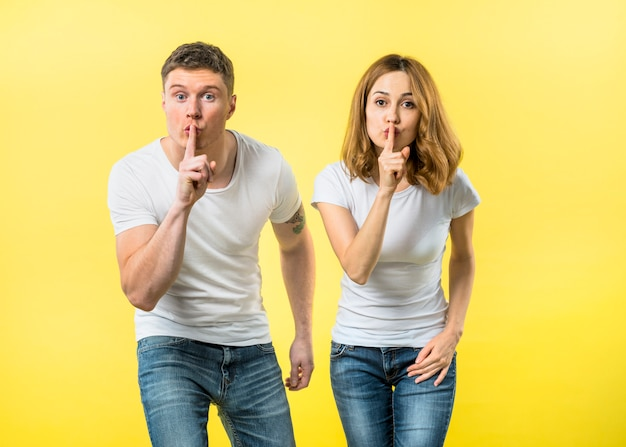 Portrait of a young couple making silence gesture by keeping finger over her lips