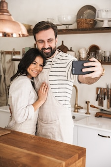 Portrait of young couple man and woman 30s wearing aprons taking selfie photo while cooking pastry with flour and eggs in kitchen at home