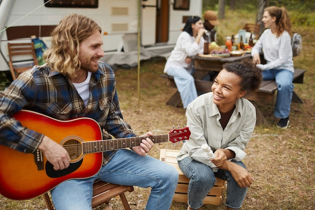 Portrait of young couple playing guitar while camping with friends in forest copy space