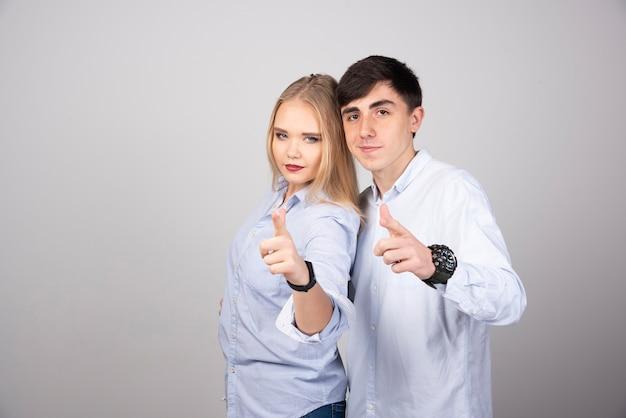 Ritratto di una giovane coppia che punta il dito isolato sul muro grigio.