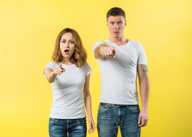 Portrait of a young couple pointing fingers toward camera against yellow backdrop