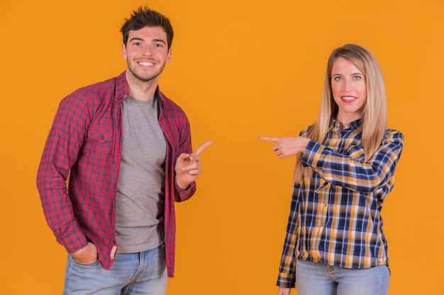 Portrait of a young couple pointing their fingers to each other against an orange backdrop